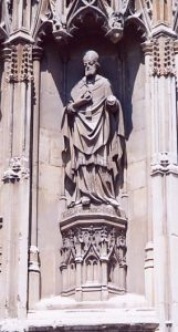 A statue of St Anselm, archbishop of Canterbury, on the exterior wall of Canterbury Cathedral, Canterbury, Kent, England, UK. He holds his work Cur Deus Homo and stands on a plinth inscribed in Latin anselmvs archiepisc. His left hand has broken off.