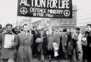 Bertrand Russell & his wife Edith Russell lead anti-nuclear march by the Committee of 100 in London on Sat 18 Feb 1961 along with Michael Randle (2nd left), Rev Michael Scott (next right), Ralph Schoenman (next to Edith Russell), Ian Dixon (holding banner, right) and Terry Chandler (far right). A rally in Trafalgar Square was followed by peaceful sit-down Committee of 100 protest at Defence Ministry against Polaris missiles being delivered to River Clyde.