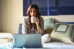 woman studying on bed with coffee in hand