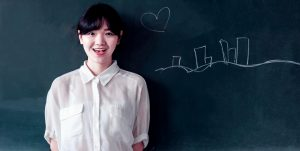 Young Woman Smiling at Chalkboard