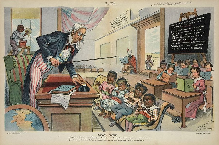 "Uncle Sam as a teacher, standing behind a desk in front of his new students who are labeled ""Cuba, Porto [i.e. Puerto] Rico, Hawaii, [and] Philippines""; they do not look happy to be there. At the rear of the classroom are students holding books labeled ""California, Texas, New Mexico, Arizona, [and] Alaska"". At the far left, an African American boy cleans the windows, and in the background, a Native boy sits by himself, reading an upside-down book labeled ""ABC"", and a Chinese boy stands just outside the door. A book on Uncle Sam's desk is titled ""U.S. First Lessons in Self-Government""."
